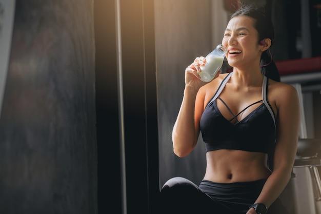 フィットネスジムでのトレーニング後にプロテインパウダーミルクセーキを飲むスポーツウェアの幸せな女性