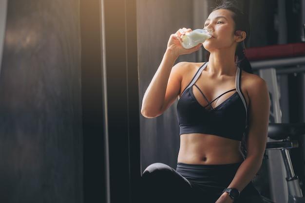 Женщина счастья в спортивной одежде пьет протеиновый порошковый молочный коктейль после тренировки в фитнес-зале