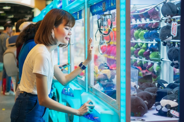Happiness woman playing claw game or cabinet to catch the dolls