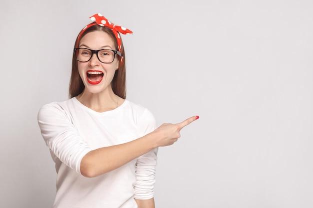 Счастье, интересно портрет красивой эмоциональной молодой женщины в белой футболке с веснушками, очками, красными губами и головной повязкой, указывающей copyspace. внутренний выстрел, изолированные на светло-сером фоне.