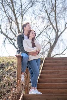 幸福。晴れた日を楽しんでいる屋外の階段でハンサムな生姜髪の女性を抱き締める若い大人の男