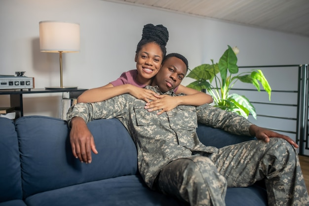 Happiness. young beautiful african american wife hugging by shoulders of military husband in uniform of come home happy together