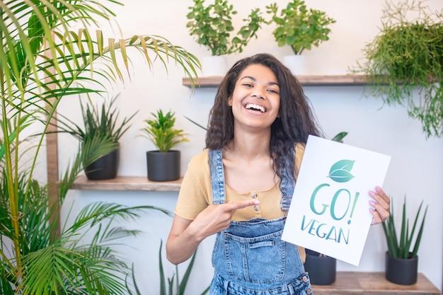 Счастье. молодая счастливая эмоциональная женщина-мулат, указывая на плакат-веган, стоящий в помещении со смехом комнатных растений