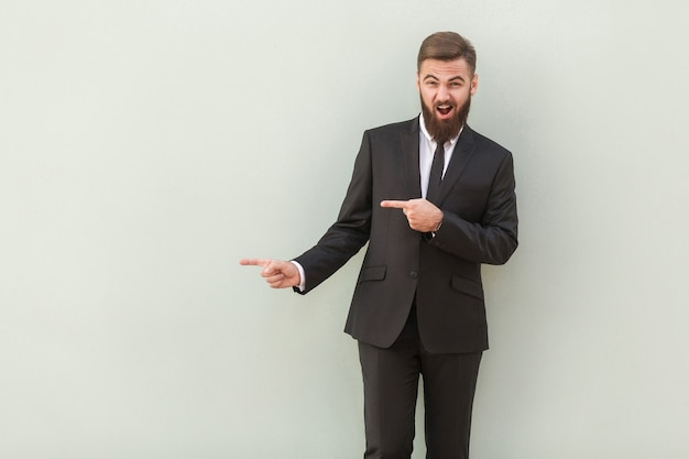Happiness young man in office wear pointing at copy space