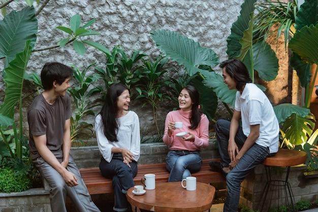 ホームガーデンのテーブルと木製のベンチに座っておしゃべり幸せの若者たち