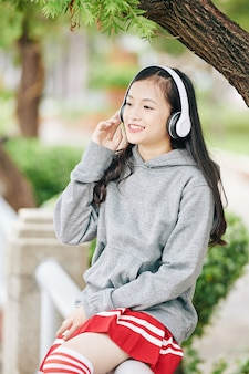 屋外で休んでいるときにヘッドフォンで良い音楽を楽しんでいるかわいいアジアの女子大生を幸せ