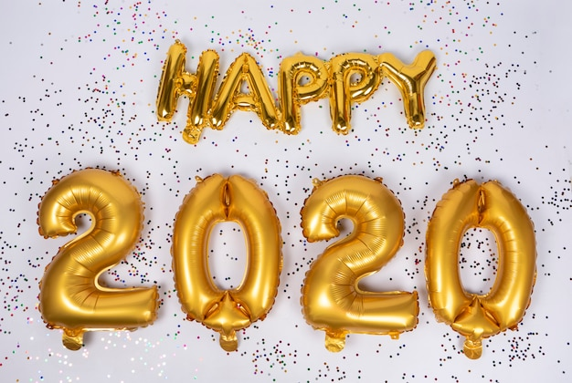 Happy 2020 lettering of frustrated gold balloons isolated with colorful confetti