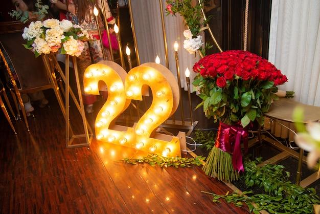 행복한 22 세 축하. 22 빛과 빨간 장미 꽃다발과 나무로 조각.