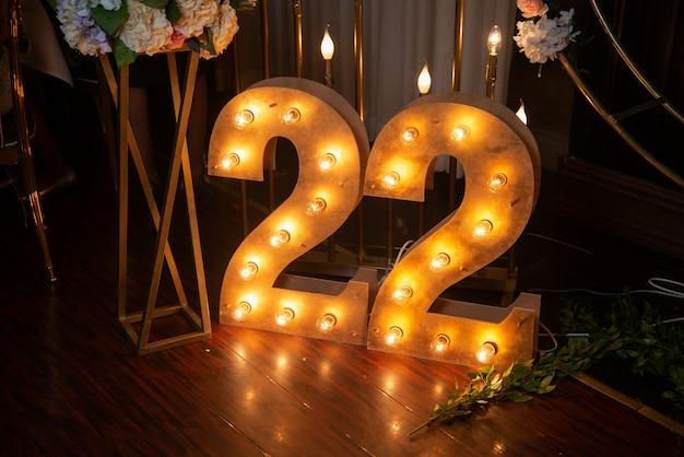 幸せな22歳のお祝い。番号22は、光で木から刻まれました。誕生日の室内装飾