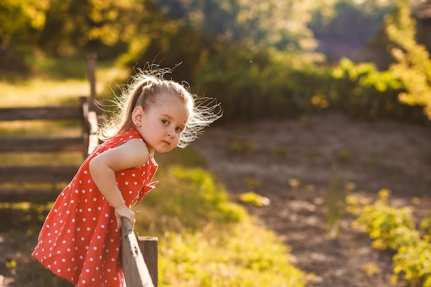 Happy 3 years old girl in red dress is playing in village summer garden portrait of little girl chi