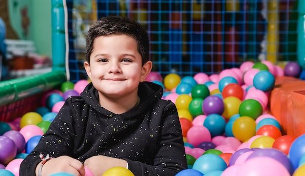 Счастливый 5-летний мальчик с маской в бассейне с шариками, так счастлив