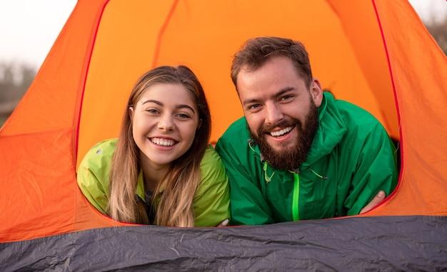 キャンプテントで休んでいる幸せなアクティブなカップル