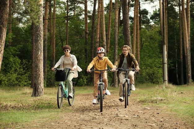 夏の日に松の木の幹や他の木々の森の小道に沿って自転車に乗る若い夫、妻、息子の幸せなアクティブな家族