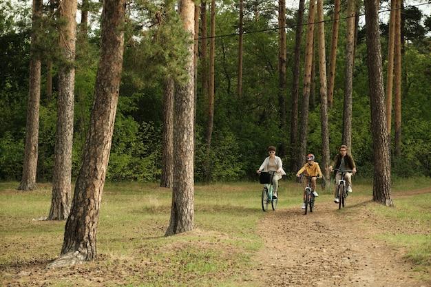 松の木の幹に囲まれた森の小道に沿って前進しながら自転車に座っている若い親とその息子の幸せなアクティブな家族