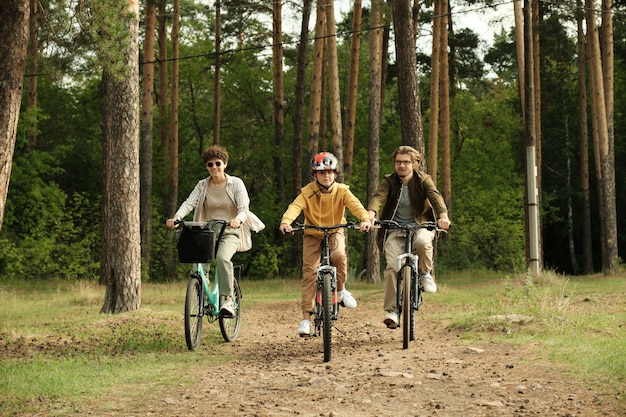 Happy active family of young husband, wife and son riding bicycles along forest path on pinetree trunks and other trees on summer day