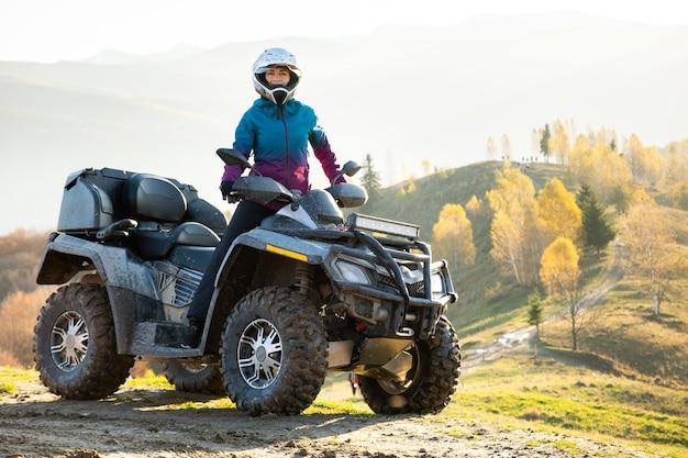 해질녘 가을 산에서 atv 쿼드 오토바이를 타고 극도의 라이딩을 즐기는 보호용 헬멧을 쓴 행복한 활동적인 여성 운전자.