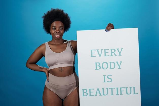Счастливая активная женщина больших размеров держит плакат с надписью:
