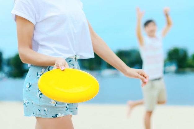 幸せなアクティブな笑顔のロマンチックなカップルがフリスビーの女の子を投げるディスクゲーム