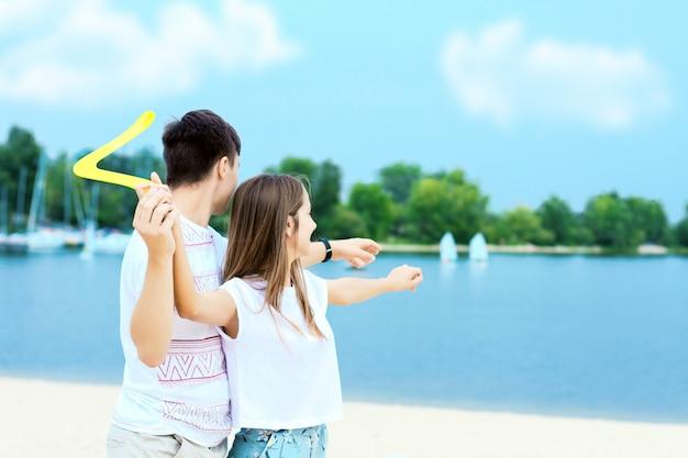 幸せなアクティブな笑顔のロマンチックなカップルが砂浜でブーメランゲームをスイングします。