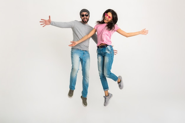 Happy active stylish man and woman jumping together isolated