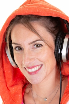 Happy active woman smiles with headphones on head looking at camera dressed in orange hoodie isolated on white