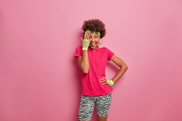 Happy active woman with afro hairstyle looks through fingers, dressed in casual comfortable clothes, has positive smile on face