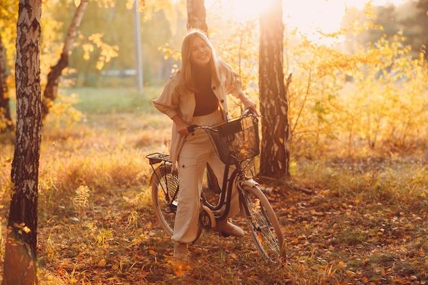日没時に秋の公園でビンテージ自転車に乗って幸せなアクティブな若い女性