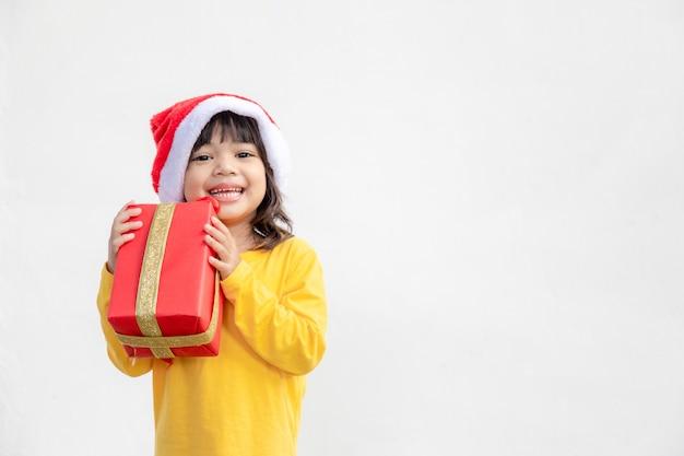 Счастливая очаровательная азиатская детская девочка с рождественским подарком в руках на белом фоне