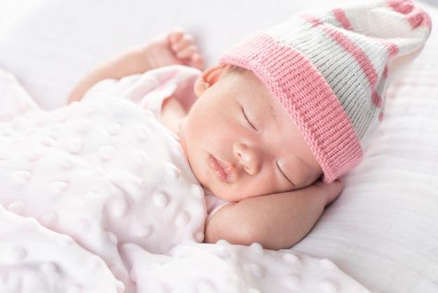 Счастливый очаровательны девочка спит в кроватке. маленький ребенок, имеющий дневной сон в постели родителей
