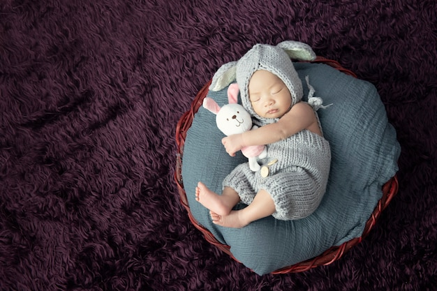 Happy adorable baby girl sleeping with doll in small bed.