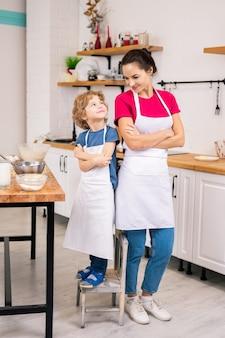 幸せな愛らしい男の子と彼の母親は、キッチンでお互いを見ながら胸に腕を組んで白いエプロンで