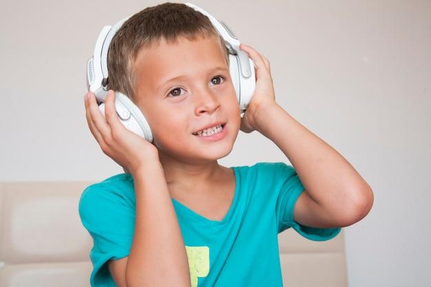 ヘッドフォンを身に着けている青いシャツの幸せな愛らしい男の子。子供は音楽を楽しんでいます。
