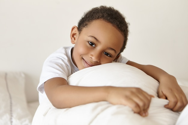 Happy adorable dark skinned boy of african origin relaxing in bed at weekend after awakening