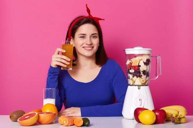 Happy adorable female holds glass of orange smoothie in her hand, a lot of ingredients to mix and eat. smiling woman keeps to healthy diet, isolated on pink. healthy lifestyle concept.