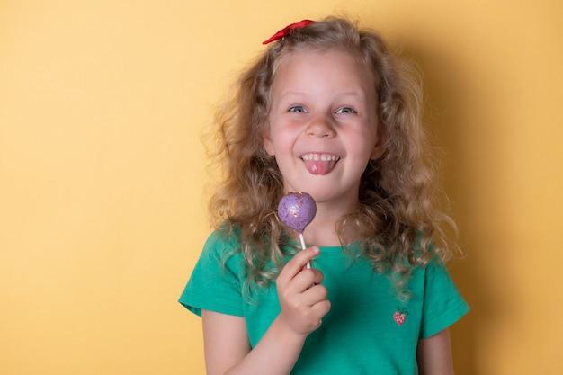 幸せな愛らしい少女は舌を示し、おいしいケーキポップ、棒でお菓子を食べます。幸せな子供時代。黄色の壁