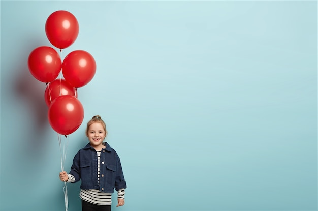 Felice ragazza adorabile con palloncini, ha un aspetto divertente, vestita con abiti di jeans, si trova sopra il muro blu con spazio libero sul lato destro per i tuoi contenuti promozionali. il bambino si diverte alla festa