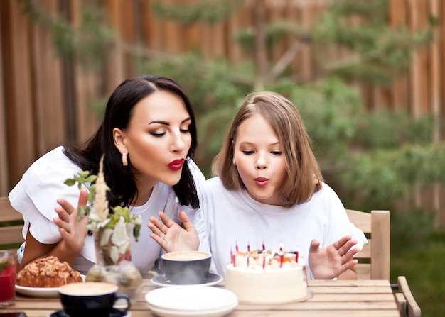 Happy adorable girl with mom celebrate with birthday cake in cafe terrace. 10 year old celebrate birthday.