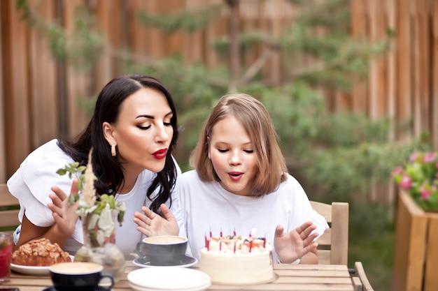 ママと幸せな愛らしい女の子は、カフェテラスでバースデーケーキで祝います。 10歳は誕生日を祝います。
