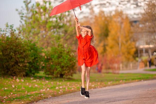 秋に赤い傘で幸せな愛らしい子供