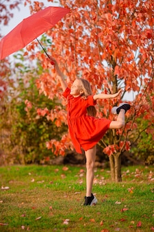 Happy adorable kid with red umbrella at autumn