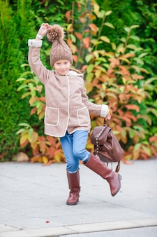 Happy adorable little girl having fun outdoors at beautiful autumn day