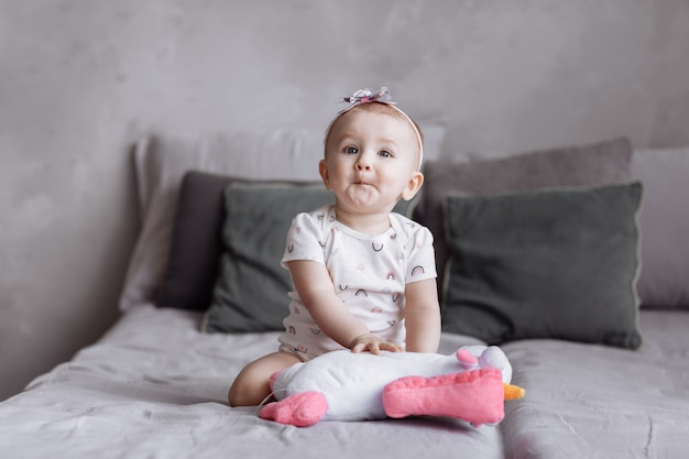Happy adorable little girl is playing with toy unicorn on bed at home.