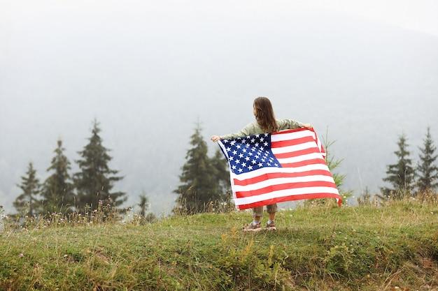 웃 고 미국 국기를 흔들며 행복 사랑스러운 작은 소녀. 7 월 4 일을 축하합니다. 독립 기념일 개념.