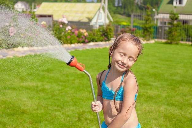 Happy adorable little girl smiling and pouring water from a hose