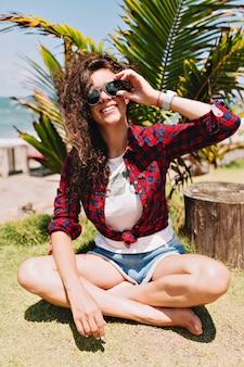 곱슬 검은 머리를 가진 행복 사랑스러운 세련된 예쁜 여자는 햇빛, 휴가, 여행, 스파 리조트에서 손바닥으로 녹색 땅에 앉아 흰색 티셔츠와 데님 반바지를 입고