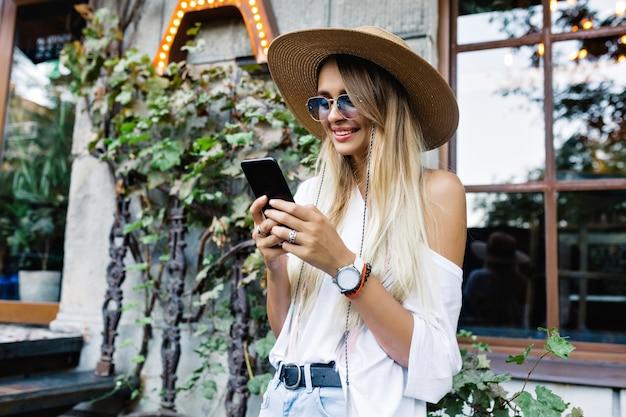幸せな笑顔の屋外の服を着たシャツとショートパンツ、帽子とスタイリッシュなサングラス、幸せな笑顔、夏とスマートフォンをスクロールする幸せな愛らしい女性