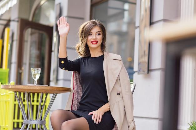 Donna adorabile felice che saluta ad un amico mentre è seduto nella caffetteria estiva con un bicchiere di vino