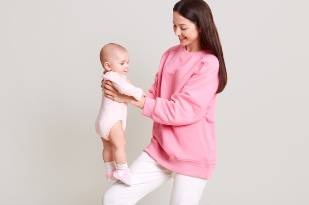 Happy adorable young dark haired female holding baby girl on her leg, charming infant in bodysuit standing on mother knee and looking away isolated over white wall.
