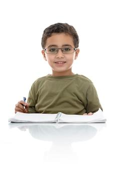 勉強して幸せな愛らしい若い少年