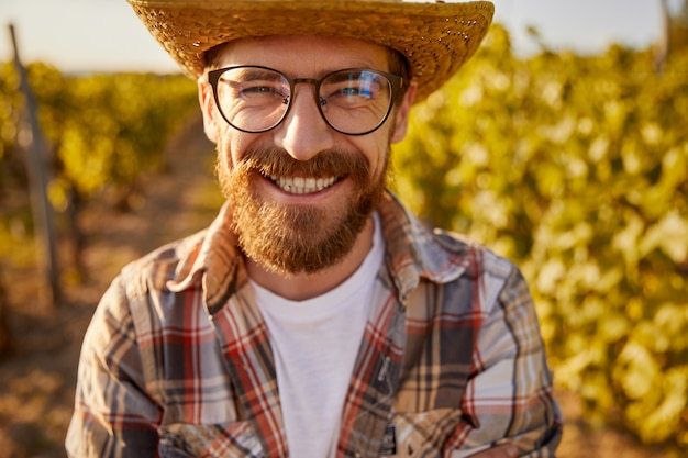 Happy adult bearded agricultural business owner in checkered shirt and straw hat with eyeglasses smiling brightly and looking at camera, while standing in vineyard in summertime